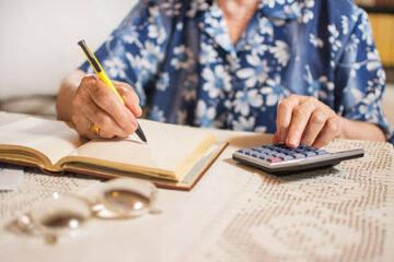 Close-up of unrecognizable senior woman doing finances at home.